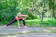 El retrato de la mujer deportiva que hace estirar ejercita en parque antes de entrenar Atleta de sexo femenino que se prepara par Fotos de archivo libres de regalías