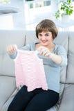 El retrato de la mujer embarazada sonriente que detiene al bebé viste Foto de archivo libre de regalías