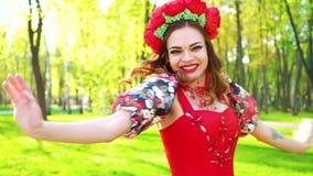 El retrato de la mujer en traje brillante y con el anillo de la flor realiza danza popular almacen de metraje de vídeo