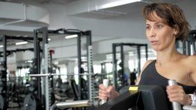 El retrato de la mujer está haciendo los ejercicios para los músculos de la espina dorsal en remar la máquina almacen de metraje de vídeo