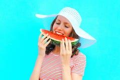 el retrato de la mujer feliz está comiendo una rebanada de sandía en un sombrero de paja Fotografía de archivo