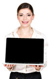 La mujer sostiene el ordenador portátil con la pantalla en blanco Imagen de archivo libre de regalías