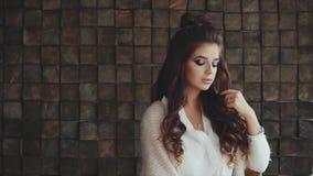 El retrato de la mujer hermosa joven con brillante compone esperar alguien metrajes