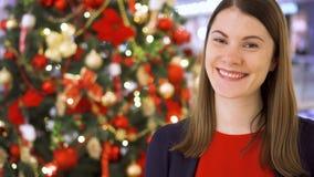 El retrato de la mujer joven alegre cerca adornó el árbol de navidad Situación y sonrisa bastante femeninas metrajes