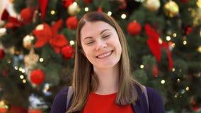 El retrato de la mujer joven alegre cerca adornó el árbol de navidad Situación y sonrisa bastante femeninas almacen de video