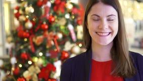 El retrato de la mujer joven alegre cerca adornó el árbol de navidad Situación y sonrisa bastante femeninas almacen de metraje de vídeo