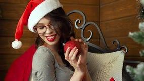 El retrato de la mujer joven alegre cerca adornó el árbol de navidad Sonrisa bastante femenina Celebración del Año Nuevo almacen de video