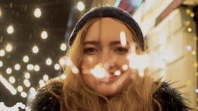 El retrato de la mujer joven alegre con las bengalas en manos se cierra para arriba Las chispas dispersan en diversas direcciones metrajes