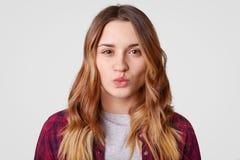 El retrato de la mujer joven con la piel sana, mantiene los labios redondeados, quiere besar al novio, tiene pelo ondulado largo, fotografía de archivo