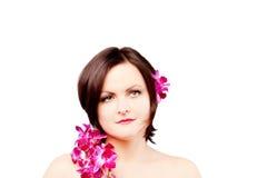 Mujer joven de la belleza con las flores rosadas de la orquídea Fotos de archivo libres de regalías