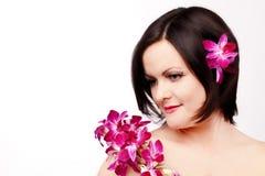 Muchacha de la belleza con las flores rosadas de la orquídea Foto de archivo