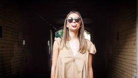 El retrato de la mujer joven elegante en las gafas de sol que soplan la goma burbujea en la calle Imagenes de archivo