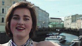 El retrato de la mujer joven en vestido manchado canta a lo largo del río en viejo centro de ciudad almacen de metraje de vídeo
