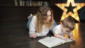 El retrato de la mujer joven est? leyendo un libro con su peque?o hijo almacen de video