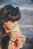El retrato de la mujer joven gorda hermosa sonriente feliz en la camiseta blanca que bebe el café dulce a través de una paja al a Fotos de archivo libres de regalías