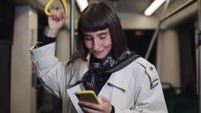 El retrato de la mujer joven hermosa sonriente en transporte público sostiene la barandilla y la ojeada en smartphone amarillo Ci almacen de metraje de vídeo