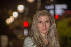 El retrato de la mujer joven rubia atractiva con la ciudad borrosa se enciende Fotos de archivo libres de regalías