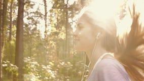 El retrato de la mujer joven rubia atractiva que corre en el bosque contra verde sale del fondo almacen de video