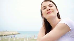 El retrato de la mujer joven se sienta en la playa Viento del mar Mediterráneo que sopla su pelo en la cámara lenta metrajes