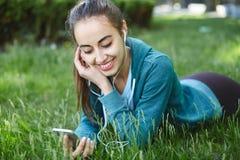 El retrato de la mujer joven y deportiva en ropa de deportes miente con el smartphone en la hierba en parque Imagen de archivo