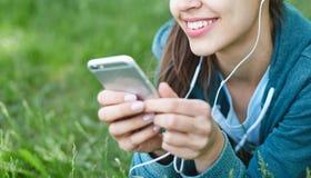 El retrato de la mujer joven y deportiva en ropa de deportes miente con el smartphone en la hierba en parque Fotos de archivo libres de regalías