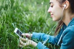 El retrato de la mujer joven y deportiva en ropa de deportes miente con el smartphone en la hierba en parque Fotografía de archivo libre de regalías