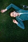El retrato de la mujer joven y deportiva en ropa de deportes miente con el smartphone en la hierba en parque Foto de archivo