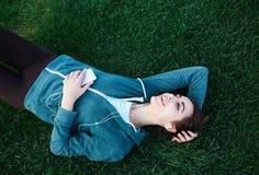 El retrato de la mujer joven y deportiva en ropa de deportes miente con el smartphone en la hierba en parque Foto de archivo libre de regalías