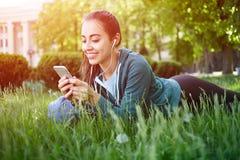 El retrato de la mujer joven y deportiva en ropa de deportes miente con el smartphone en la hierba en parque Imágenes de archivo libres de regalías