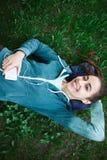 El retrato de la mujer joven y deportiva en ropa de deportes miente con el smartphone en la hierba en parque Fotografía de archivo