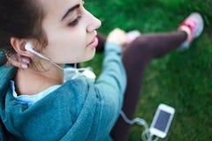El retrato de la mujer joven y deportiva en ropa de deportes miente con el smartphone en la hierba en parque Imagen de archivo libre de regalías