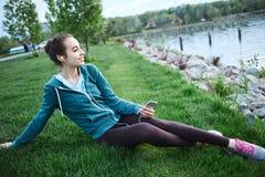 El retrato de la mujer joven y deportiva en ropa de deportes miente con el smartphone en la hierba en parque Fotos de archivo