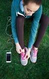 El retrato de la mujer joven y deportiva en ropa de deportes se sienta con el smartphone en la hierba en parque Imagen de archivo libre de regalías
