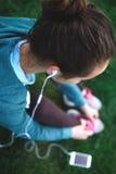 El retrato de la mujer joven y deportiva en ropa de deportes se sienta con el smartphone en la hierba en parque Fotografía de archivo libre de regalías