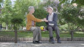 El retrato de la mujer mayor adorable con el ramo de flores amarillas se sienta en el banco con un viejo hombre y las manos el so almacen de metraje de vídeo