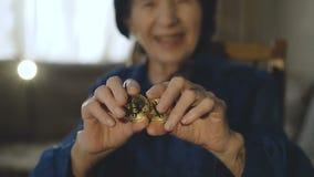 El retrato de la mujer mayor lleva a cabo dos bitcoins de oro en manos en la cámara almacen de metraje de vídeo