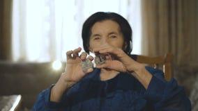 El retrato de la mujer mayor lleva a cabo dos bitcoins de plata en manos en la cámara almacen de metraje de vídeo