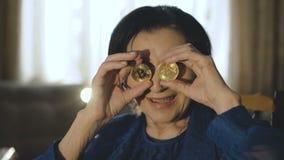 El retrato de la mujer mayor pone dos bitcoins de oro a los vidrios y a las sonrisas almacen de video