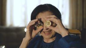 El retrato de la mujer mayor pone dos bitcoins de oro a los vidrios y a las sonrisas metrajes