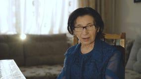 El retrato de la mujer mayor sonriente pone los vidrios y mira la cámara almacen de metraje de vídeo