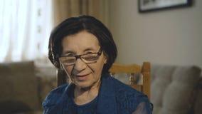 El retrato de la mujer mayor sonriente pone los vidrios y mira la cámara metrajes