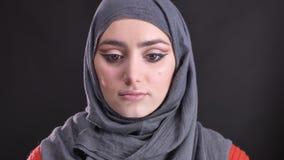 El retrato de la mujer musulmán hermosa en hijab con maquillaje brillante y brillante aumenta sus ojos y relojes tranquilamente e almacen de video