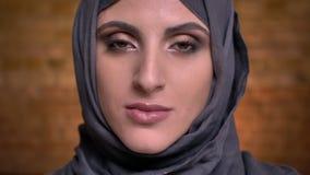El retrato de la mujer musulmán de mediana edad seria en hijab con maquillaje brillante que mira tranquilamente en cámara encendi metrajes