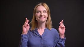 El retrato de la mujer rubia caucásica atractiva que gesticula los cruzar-fingeres firma para mostrar esperanza en fondo negro metrajes