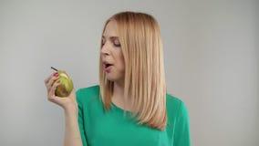 El retrato de la mujer rubia come la pera en el fondo blanco metrajes