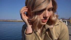 El retrato de la mujer rubia joven atractiva en foso con la maleta del vintage se está sentando en el embarcadero del jacht almacen de metraje de vídeo