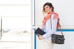 El retrato de la mujer turística joven que sostiene un libro y la cámara empaquetan Foto de archivo