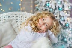 El retrato de la niña bonita se sienta y sueña en una silla en tiempo de la Navidad Imagen de archivo