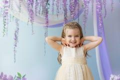 El retrato de la niña en un vestido amarillo en un cuarto adornó lilas Fotografía de archivo