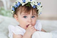 El retrato de la niña en un vestido blanco y con una diadema en una cabeza se lame los fingeres Foto de archivo libre de regalías